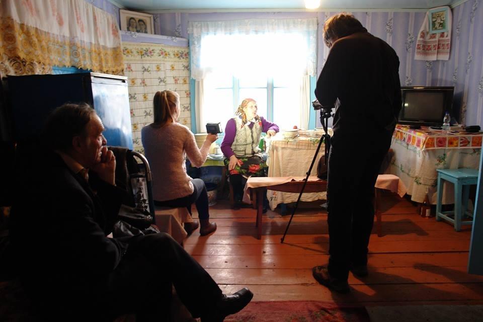 Олексій Нагорнюк спиною до нас. Записує розповідь жінки. Напевне на Поліссі. Фото з його  сторінки у facebook.